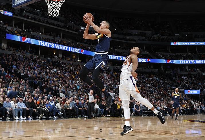 Denver Nuggets forward Michael Porter Jr., left, goes up for a basket past Phoenix Suns forward Elie Okobo in the first half of an NBA basketball game Sunday, Nov. 24, 2019, in Denver. (AP Photo/David Zalubowski)