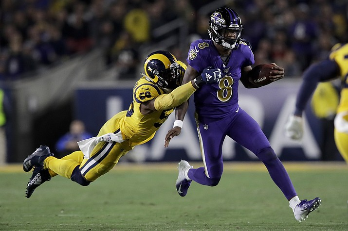 Baltimore Ravens quarterback Lamar Jackson, right, is tackled by Los Angeles Rams defensive end Dante Fowler during the second half of a game Monday, Nov. 25, 2019, in Los Angeles. (Marcio Jose Sanchez/AP)