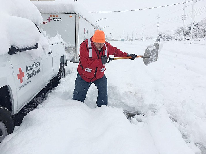 Howard King of Kingman shovels snow for the American Red Cross after a storm last winter in Kingman. There's a chance of snow this week. (Photo courtesy of American Red Cross)