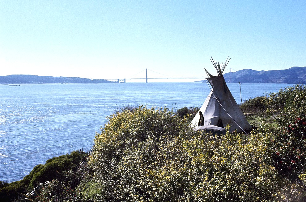 FILE - In this Nov. 18, 1970, file photo, Sioux Indian John Trudell stands next to the teepee he set up for himself during the Native American occupation of Alcatraz Island. The week of Nov. 18, 2019, marks 50 years since the beginning of a months-long Native American occupation at Alcatraz Island in the San Francisco Bay. The demonstration by dozens of tribal members had lasting effects for tribes, raising awareness of life on and off reservations, galvanizing activists and spurring a shift in federal policy toward self-determination. (AP Photo/File)