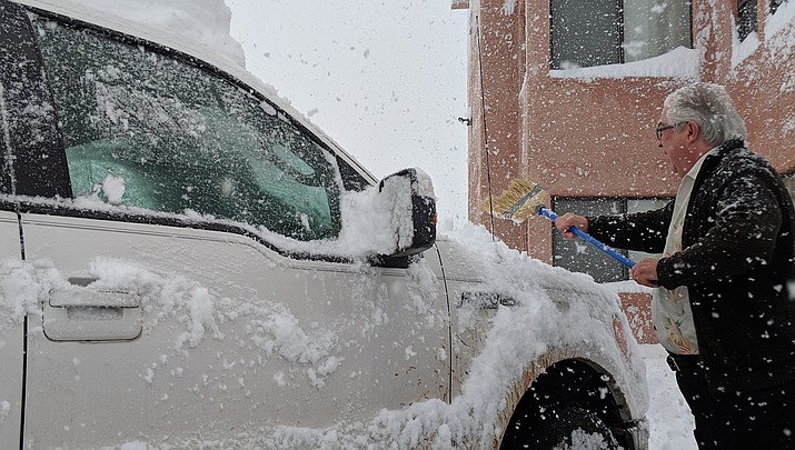 A motorist clears snow from a vehicle in Kingman last winter. Heavy snow was already causing mayhem in Colorado and Wyoming on Tuesday, Nov. 26, and the Kingman area is expected to see snow later this week. (Miner file photo)