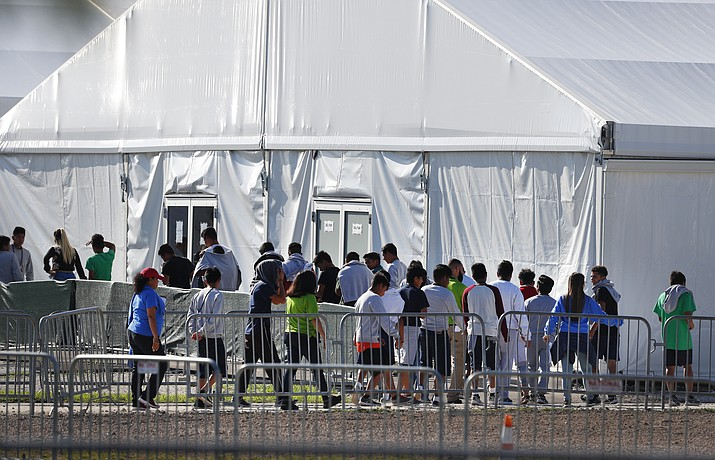 In this Feb. 19, 2019, file photo, children line up to enter a tent at the Homestead Temporary Shelter for Unaccompanied Children in Homestead, Fla. The U.S. government didn't have the technology needed to properly document and track the thousands of immigrant families separated at the southern border in 2018. That's according to a new report by an internal government watchdog. (AP Photo/Wilfredo Lee, File)