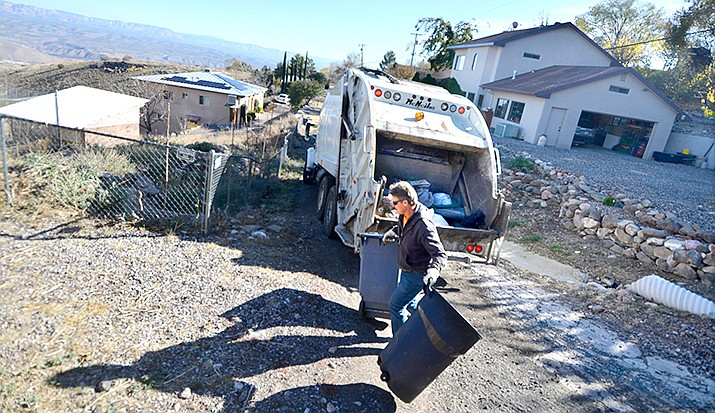 Troy Marsh loads trash into the Town of Jerome's garbage truck on Monday morning. Collecting trash on the steep streets in the area is a challenge, but one that gets easier with practice. VVN/Vyto Starinskas