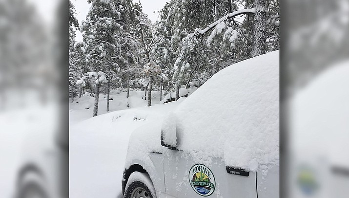 Fresh snow covers a Mohave County Parks Department pickup truck at Hualapai Mountain Park on Friday, when more than a foot of fresh snow fell. County Parks has purchased a snowmaking machine to assure there's snow on the ground for the 2019 Winter Wonderland on Saturday, Dec. 14. (Mohave County Parks photo)