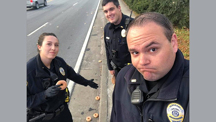 "A Facebook post from Brookhaven police shows officers respond to the scene of ""total carnage"" Tuesday morning. It says dozens of doughnuts fell from a delivery truck onto the curb and into the gutter of a road in the city near Atlanta. (Brookhaven, GA Police Department, Facebook)"