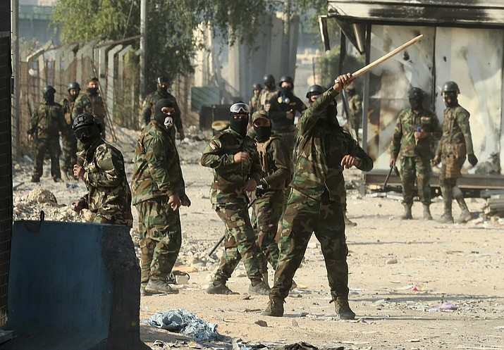 Security forces try to disperse anti-government protesters during clashes in Baghdad, Iraq, Saturday. (Hadi Mizban/AP)