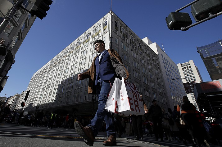 A man carries shopping bags across the street from a Macy's store in San Francisco, Friday, Nov. 29, 2019. Black Friday once again kicked off the start of the holiday shopping season. (AP Photo/Jeff Chiu)