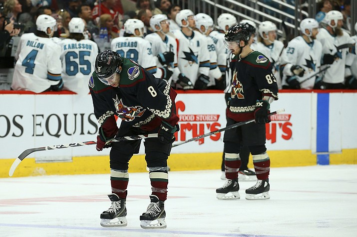 Arizona Coyotes center Nick Schmaltz (8) and right wing Conor Garland (83) pause on the ice after a goal scored by San Jose Sharks' Dylan Gambrell during the second period of a game Saturday, Nov. 30, 2019, in Glendale. (Ross D. Franklin/AP)