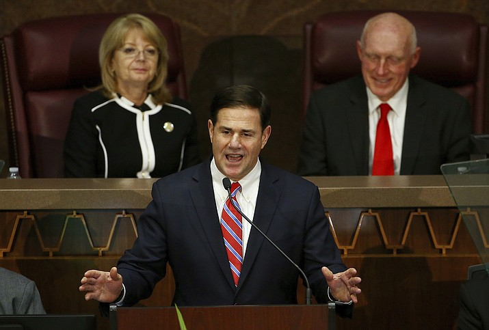 In this Jan. 14, 2019 photo, Arizona Republican Gov. Doug Ducey, center, speaks during his state of the state address as Senate President Karen Fann, R-Prescott, left, and House Speaker Rusty Bowers, R-Mesa, right, listen in Phoenix. Ducey will give his 2020 state of the state on Monday, Jan. 13, 2020, and is expected to focus on individual tax cuts. (Ross D. Franklin/AP, File)