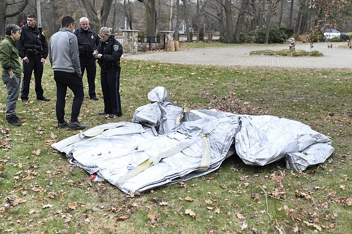 In this Sunday, Dec. 1, 2019 photo provided by Kevin Brown, police officers talk to Stephanie Leguia and Wenhan Huang beside an evacuation slide that fell from a jetliner into the yard of a home in Milton, Mass. A Delta Air Lines spokeswoman said the uninflated slide fell from a flight from Paris to Boston midday as it approached for a landing. Authorities say no one was hurt. (Kevin Brown via AP)
