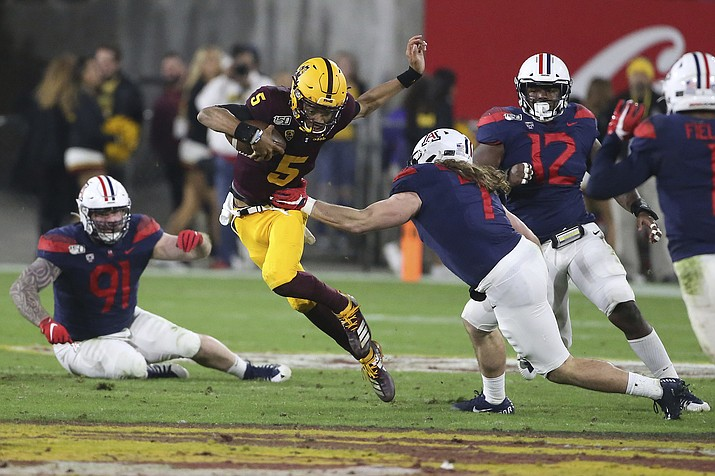 Arizona State's Jayden Daniels (5) runs against Arizona's defense during the first half of an NCAA college football game, Saturday, Nov. 30, 2019, in Tempe, Ariz. (AP Photo/Darryl Webb)