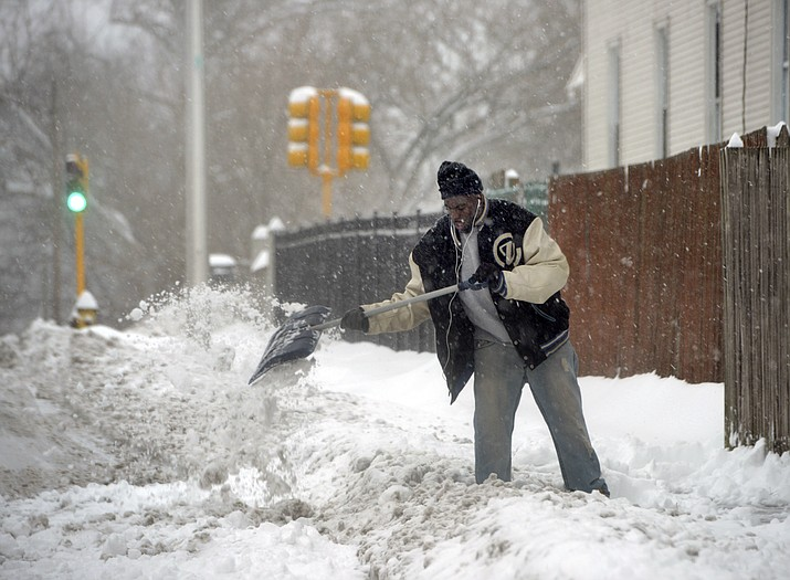 Rashad Taylor clears snow on Genesee Street in Springfield's Liberty Heights neighborhood after an overnight snowstorm, Monday, Dec. 2, 2019, in Springfield, Mass. (Don Treeger/The Republican via AP)