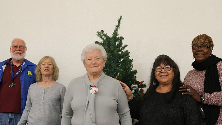 Volunteers pose in front of the City of Kingman Senior Angel tree in this Dec. 23, 2018 photo. Persons interested in helping a local senior citizen in need this Christmas can pick up a wish to fill at the Angel Tree at the main city office at 310 N. Fourth St. in Kingman. (Miner file photo)