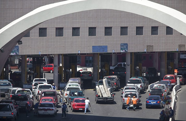 This June 1, 2009, file photo shows vehicles waiting to enter the U.S. through The Dennis DeConcini Port of Entry in downtown Nogales, Ariz. For months, the U.S. has barred asylum seekers from approaching official crossings to file a claim. Now, some are rushing the ports by running through vehicle lanes to evade the process used to officially request asylum. That is causing massive delays at crossings in Arizona as U.S. Customs and Border Protection officials have barricaded lanes used by cars to legally enter the U.S. (Mark Henle/The Arizona Republic via AP, File)