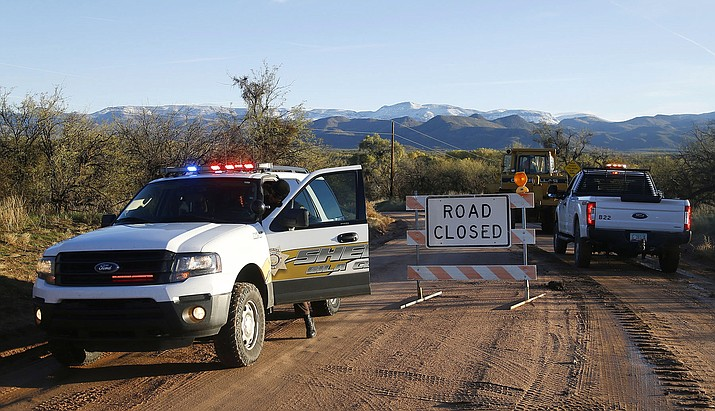 This Saturday, Nov. 30, 2019, photo shows the road closed near Bar X road and Tonto Creek after a vehicle was washed by flood waters in Tonto Basin, Ariz. Rescuers with helicopters, drones, boats and dogs searched Sunday for a 6-year-old girl missing since Friday, when a truck she was in was swept away while attempting to cross an Arizona creek swollen by runoff from a powerful storm. (Patrick Breen/The Arizona Republic via AP)