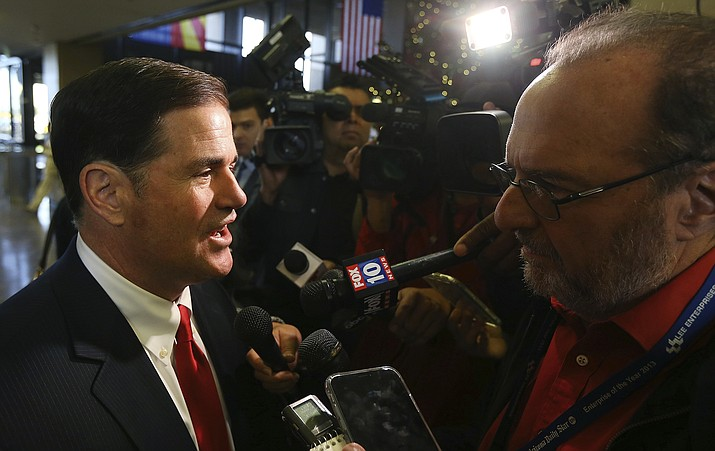 Arizona Gov. Doug Ducey speaks to reporters regarding the search for the missing child swept away in flood waters of the Tonto Creek after Ducey attended the Capitol Christmas Tree Lighting Ceremony at the Arizona Capitol Tuesday, Dec. 3, 2019, in Phoenix. (AP Photo/Ross D. Franklin)