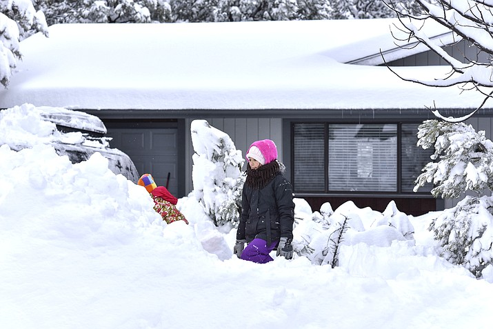 Ella Tierney, 10, and Gianna Tierney, 4, play in the snow following a winter snow storm that dropped nearly 24 inches Nov. 29 on Havasupai Street in Grand Canyon Village. (V. Ronnie Tierney/WGCN)