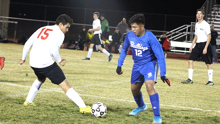 Lee Williams' Pedro Ramirez, left, and Kingman's Marcos Silva square off Tuesday during the Vols' 5-0 win at KHS. (Photo by Beau Bearden/Kingman Miner)