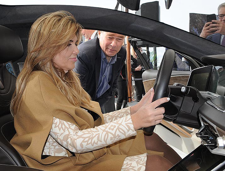 Lucid Motors CEO Peter Rawlinson shows off the model of the $100,000-plus vehicle Monday that the company plans to build in Casa Grande to Sonora Gov. Claudia Pavlovich who attended a formal ceremony to launch what company officials say will be a $700 million plant. (Capitol Media Services photo by Howard Fischer)