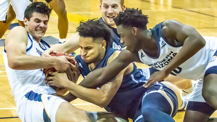 NAU forwards Brooks Debisschop, left, and Bernie Andre, right, battle for the loose ball in a game against UC Davis Wednesday, Dec. 4, 2019, in Flagstaff. (NAU Athletics/Courtesy)