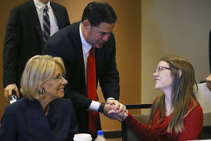 U.S. Education Secretary Betsy DeVos, left, joins Arizona Republican Gov. Doug Ducey, middle, as they talk with Grace Jones, a high school sophomore from Tucson, Ariz., after a roundtable discussion on school choice Thursday, Dec. 5, 2019, in Scottsdale, Ariz. DeVos talked with state lawmakers, educators, students and parents about her $5 billion plan to fund tuition for private school students, prior to addressing the American Legislative Exchange Council. (AP Photo/Ross D. Franklin)