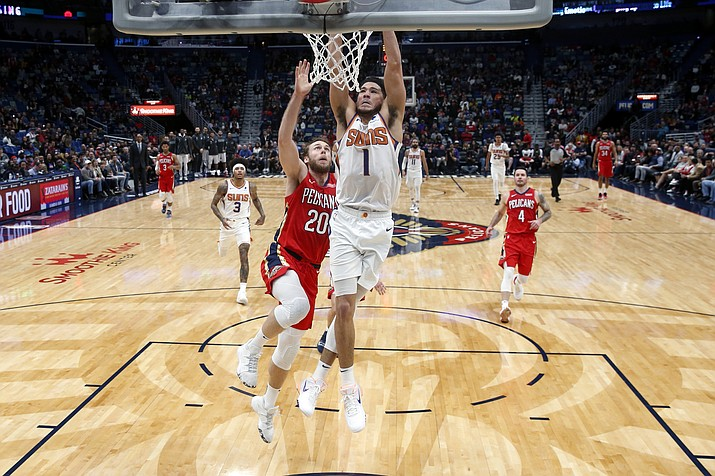 Phoenix Suns guard Devin Booker goes to the basket in front of New Orleans Pelicans forward Nicolo Melli (20) during a game in New Orleans, Thursday, Dec. 5, 2019. (Gerald Herbert/AP)