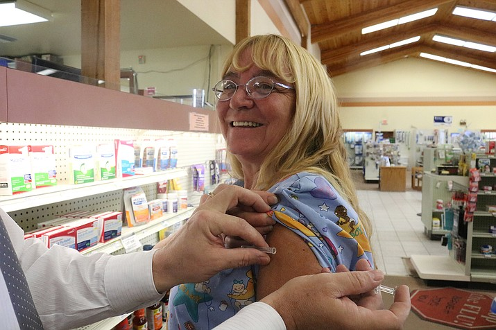 Chris Proffit, pharmacist at Uptown Drug in Kingman, demonstrates how a flu shot is administered. (Photo by Travis Rains/Kingman Miner)
