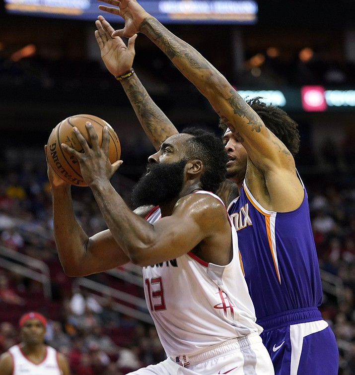 Houston Rockets' James Harden (13) goes up for a shot as Phoenix Suns' Kelly Oubre Jr. defends during the first half of a game Saturday, Dec. 7, 2019, in Houston. (David J. Phillip/AP)