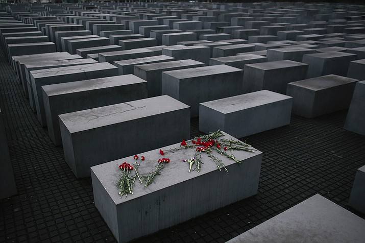In this Tuesday, Jan. 27, 2015 file photo, flowers lay on a concrete slab of the Holocaust Memorial to mark the International Holocaust Remembrance Day in Berlin. One of Germany's richest families, the Reimann family, which owns Krispy Kreme Doughnuts, Pret A Manger, Peet's Coffee and other famous international brands is giving millions to support Holocaust survivors. The family has established the Alfred Landecker Foundation in Germany to oversee the efforts, named after a German Jew who was killed by the Nazis either in Sobibor or at the Belzec Nazi death camp. (Markus Schreiber/AP, file)