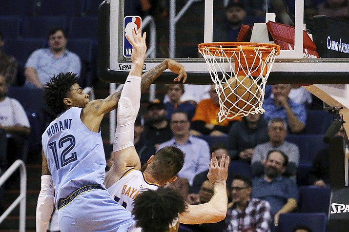 Memphis Grizzlies guard Ja Morant (12) dunks over Phoenix Suns center Aron Baynes during the second half of an game, Wednesday, Dec. 11, 2019, in Phoenix. The Grizzlies defeated the Suns 115-108. (Ross D. Franklin/AP)
