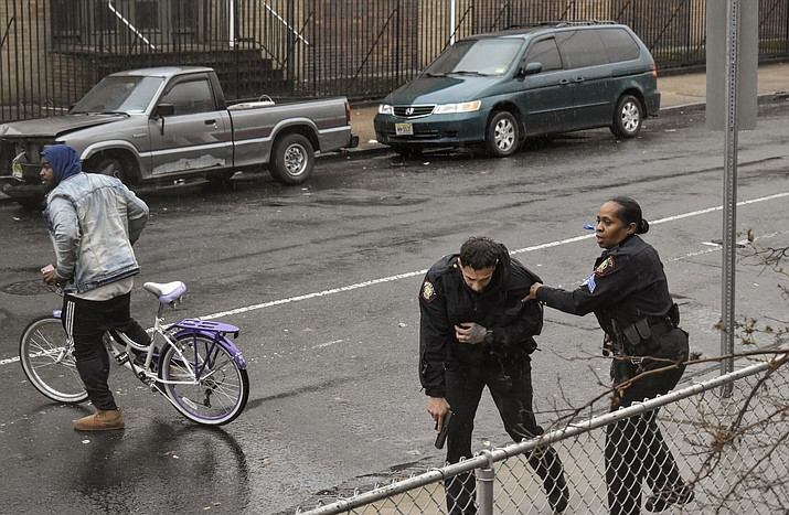 In this Dec. 10, 2019 photo, Jersey City police Sgt. Marjorie Jordan, right, helps fellow officer Raymond Sanchez to safety after he was shot during a gunfight that left multiple dead in Jersey City, N.J. The two killers were armed with a variety of weapons, including an AR-15-style rifle and a shotgun that they were wielding when they stormed into a store in an attack that left the scene littered with several hundred shell casings, broken glass and a community in mourning. Despite years of New Jersey officials focusing on the problems of crime guns coming into the state, the shooting shows efforts are falling short. (Justin Moreau via AP)