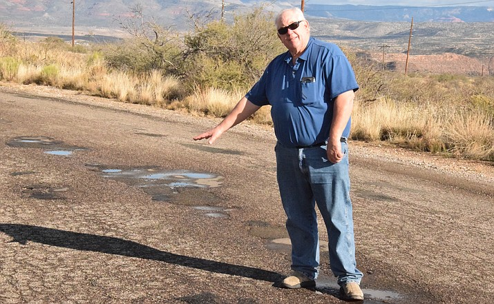 "David Brinkley points to a section of the ""good"" surface along Old Jerome Highway that will be part of three crack-sealing projects to take place in Clarkdale after temperatures warm in the spring. Clarkdale street conditions have brought flak toward the town council and staff. VVN/Jason W. Brooks"