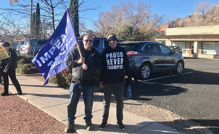 """Steve Pace of Cornville, left, holds an """"Impeach Trump"""" flag while standing next to Russ Snider of Sedona during Tuesday's MoveOn.org event in Sedona. In addition to more than 150 at the sidewalk rally in Sedona, another 60-plus people gathered in Cottonwood as part of a nationwide event. VVN/Jason W. Brooks"""