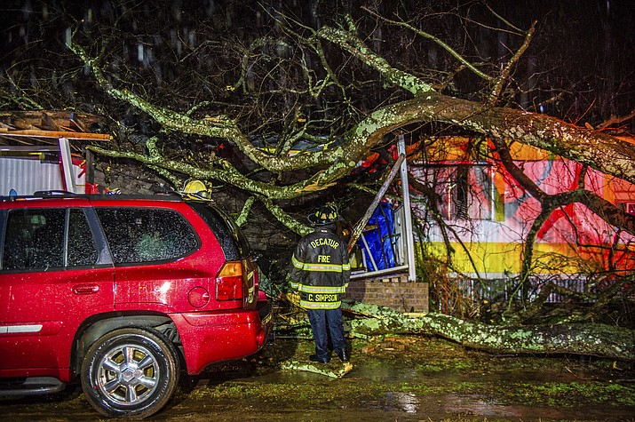 Cory Simpson of Decatur Fire & Rescue assess damage before evacuating a mobile home after a tree fell on the home in Decatur, Ala., Monday, Dec. 16, 2019. Powerful storms smashed buildings, splintered trees and downed power lines Monday around the Deep South, leaving at least one person dead as the dangerous mix of thunderstorms and suspected tornadoes raked the region in the week ahead of Christmas. (Dan Busey/The Decatur Daily via AP)