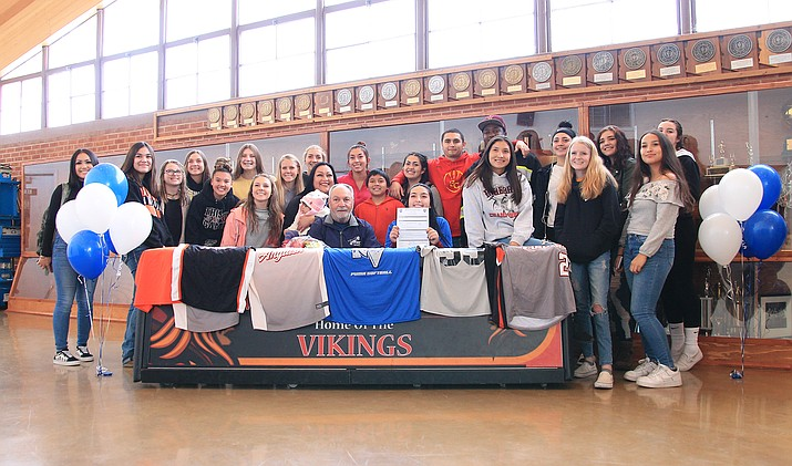 Surrounded by her Vikings teammates and parents, John and Gloria Romero, Jazlyn Romero signs a letter of intent to play softball at Paradise Valley Community College Dec. 3. Head Coach Nick Candrea attended the signing. (Loretta McKenney/WGCN)
