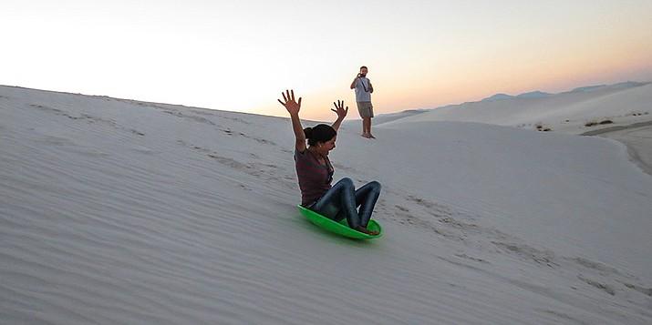 Visitors sled down the namesake white sand dunes at White Sands National Monument. (Photo/NPS)