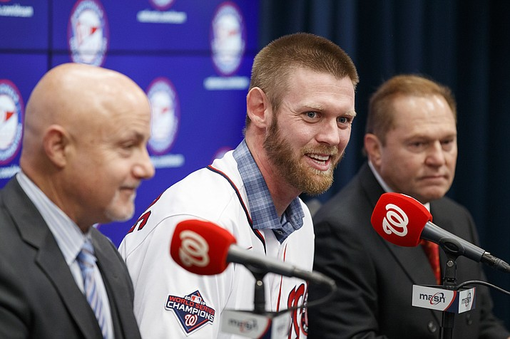 Washington Nationals pitcher Stephen Strasburg, center, speaks during a baseball media availability, accompanied by general manager Mike Rizzo, left, and agent Scott Boras, right, at Nationals Park, Tuesday, Dec. 17, 2019, in Washington. (Alex Brandon/AP)