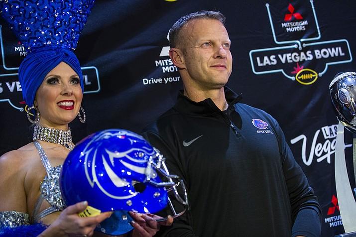 Boise State head coach Bryan Harsin poses alongside showgirl Jennifer Autry ahead of the Las Vegas Bowl game in Las Vegas, Tuesday, Dec. 17, 2019. (Chase Stevens/Las Vegas Review-Journal via AP)