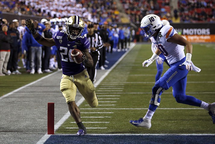 Washington running back Salvon Ahmed, left, makes it into the end zone ahead of Boise State safety Kekoa Nawahine for Washington's second touchdown during the first half of the Las Vegas Bowl at Sam Boyd Stadium, Saturday, Dec. 21, 2019, in Las Vegas. (Steve Marcus/AP)