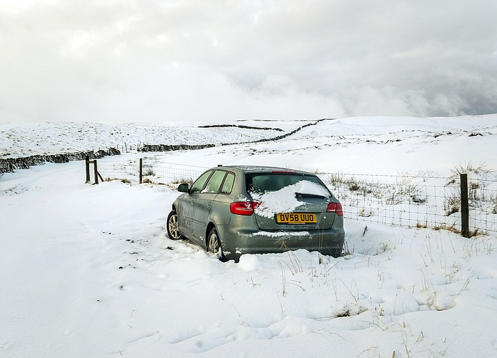 An abandoned car is seen near Fleet Moss in the Yorkshire Dales National Park on Monday, Dec. 16, 2019. Drivers in Arizona are being warned to prepare for snowfall over the next few days. (Danny Lawson/PA Wire via AP Images)