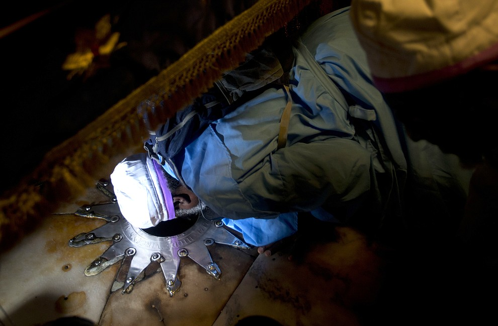 A worshipper prays inside the Church of the Nativity, built on top of the site where Christians believe Jesus Christ was born, on Christmas Eve, in the West Bank City of Bethlehem, Tuesday, Dec. 24, 2019. (AP Photo/Majdi Mohammed)