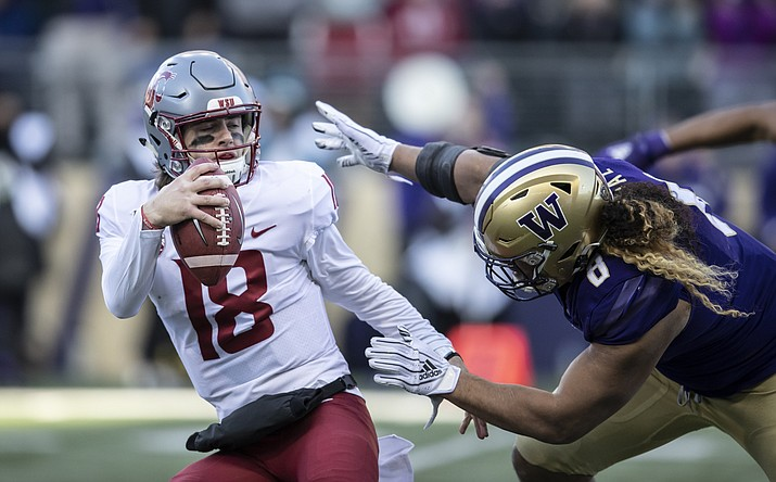 Washington State quarterback Anthony Gordon tries to escape the grasp of Washington defensive lineman Benning Potoa'e during the first half an NCAA college football game, on Friday, Nov. 29, 2019 in Seattle. (Stephen Brashear/AP, file)