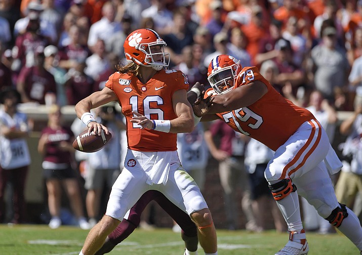 This Sept. 7, 2019, file photo shows Clemson quarterback Trevor Lawrence dropping back to pass with blocking help from Jackson Carman (79) during the second half of an NCAA college football game in Clemson, S.C. Carman is one of the few recent five-star recruits from Ohio who didn't end up at Ohio State. Now the two schools meet in the CFP semifinals, where Carman will be matched up against Ohio State's star defensive lineman Chase Young. (Richard Shiro/AP, file)