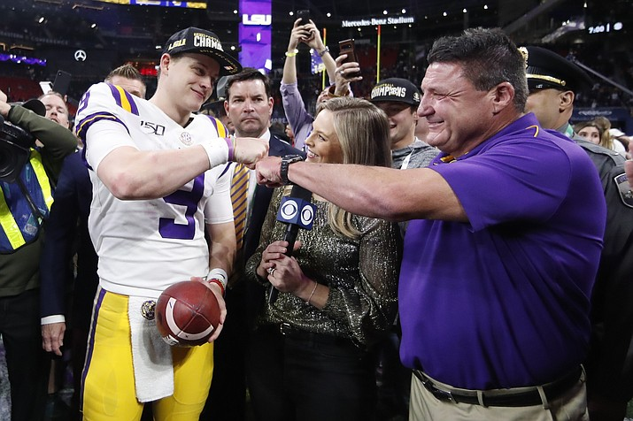 In this Dec.  7, 2019, photo, LSU quarterback Joe Burrow and LSU head coach Ed Orgeron celebrate after the Southeastern Conference championship game against Georgia, in Atlanta. Orgeron is The Associated Press Coach of the Year after leading the top-ranked Tigers to a Southeastern Conference championship. (John Bazemore/AP, file)