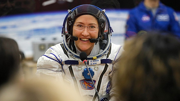 In this Thursday, March 14, 2019 file photo, U.S. astronaut Christina Koch, member of the main crew of the expedition to the International Space Station (ISS), speaks with her relatives through a safety glass prior the launch of Soyuz MS-12 space ship at the Russian leased Baikonur cosmodrome, Kazakhstan.  (Dmitri Lovetsky/AP)