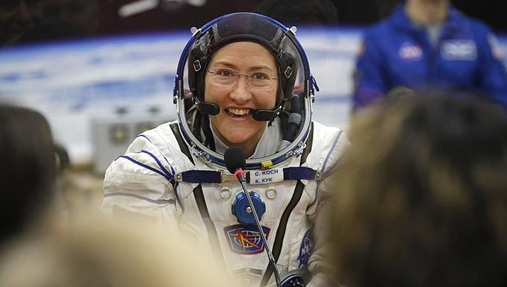In this Thursday, March 14, 2019 file photo, U.S. astronaut Christina Koch, member of the main crew of the expedition to the International Space Station (ISS), speaks with her relatives through a safety glass prior the launch of Soyuz MS-12 space ship at the Russian leased Baikonur cosmodrome, Kazakhstan. Koch will set a new record Saturday, Dec. 28, for the longest single spaceflight by a woman, breaking the old mark of 288 days with about two months left in her mission. Koch, a 40-year-old electrical engineer arrived at the International Space Station on March 14. She broke the record previously set by former space station commander Peggy Whitson in 2016-2017. (AP Photo/Dmitri Lovetsky, Pool)
