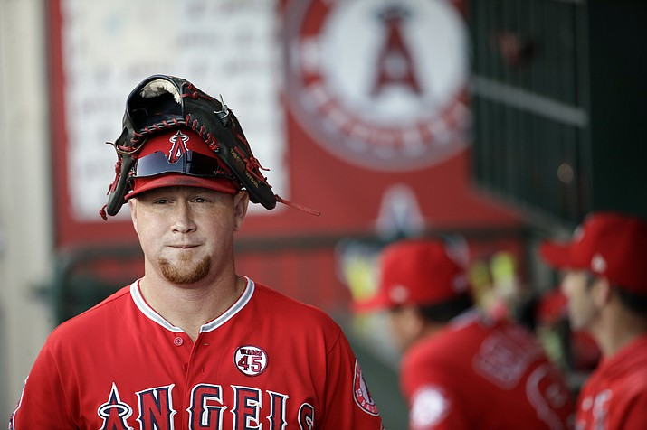 Then-Los Angeles Angel Kole Calhoun wears a glove on his head in the dugout before the start of a game against the Tampa Bay Rays, Saturday, Sept. 14, 2019, in Anaheim, Calif. (Marcio Jose Sanchez/AP)