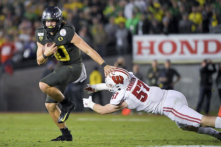 Oregon quarterback Justin Herbert runs for a touchdown past Wisconsin linebacker Jack Sanborn during second half of the Rose Bowl NCAA college football game Wednesday, Jan. 1, 2020, in Pasadena, Calif. (Mark J. Terrill/AP)