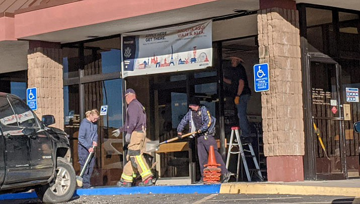 Postal workers clean up after a pickup truck struck the front entrance of the U.S. Post Office at 1901 Johnson Ave. in Kingman on Thursday, Jan. 2, 2020. (Photo by Travis Rains/Kingman Miner)