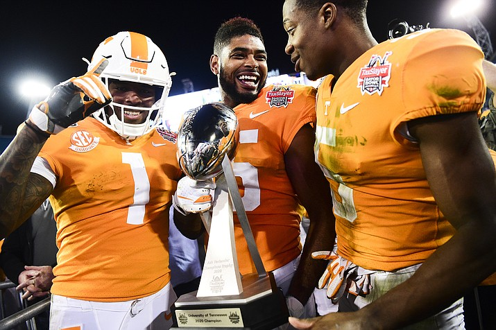 Tennessee wide receiver Jauan Jennings (15) holds the trophy next to wide receivers Marquez Callaway (1) and Josh Palmer (5) after the team's 23-22 win over Indiana in the Gator Bowl in Jacksonville, Fla., Thursday, Jan. 2, 2020. (Calvin Mattheis/Knoxville News Sentinel via AP)